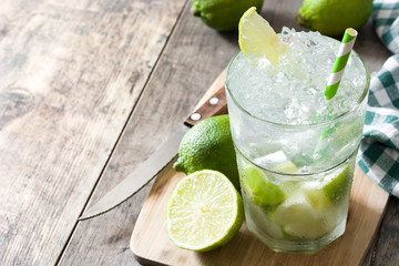 Caipirinha cocktail in glass on wooden table background. Copyspace