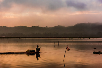 Fisherman sit on bamboo raft while waiting for sunrise