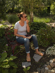 Attractive woman in the garden eating blue plums. Summertime, healthy lifestyle.