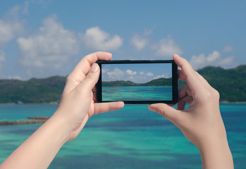 Female hand taking picture of Praslin island on mobile phone. Picture of Seychelles island on smart phone