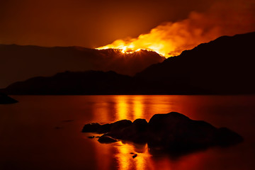 Forest fire at night reflecting in nearby lake.