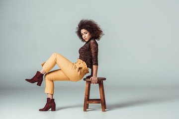 side view of african american woman in retro clothes leaning on chair on grey