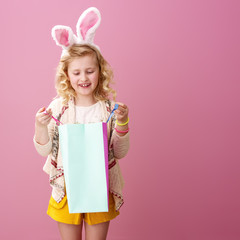 happy modern child on pink background looking at shopping bag
