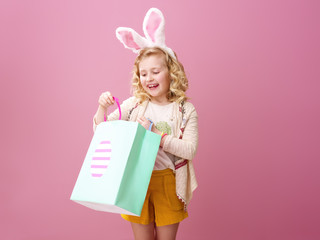 smiling girl on pink background looking at Easter shopping bag