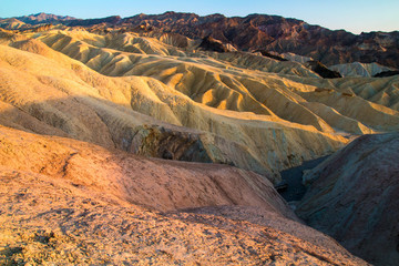 The Colorful Eroded Ridges of Zabriskie Point, dry mudstone mountains, volcanic shaped, during setting sun light, Death Valley National Park California USA