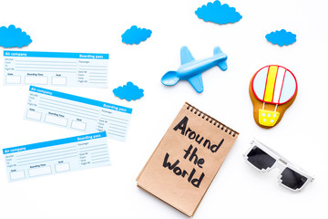 Family trip concept. Airplan toy, air balloon cookie, airplan tickets. Around the world hand lettering in notebook on white background top view