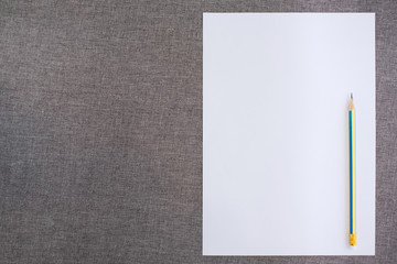 Top view of Empty paper with pencil on fabric background
