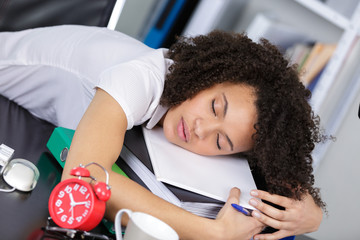 woman sleeping on top of the paperworks