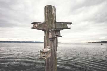 Birdhouse on wooden post by lake against cloudy sky