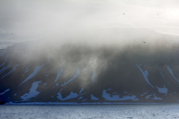 Clouds slide over from glacier and cliff to sea