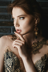 Beautiful, sexy, fashionable brunette girl with blue eyes, in gold dress with handmade gold earrings, is posing at brick wall background