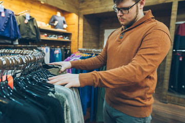 man make shopping in store. choose shirts in shop