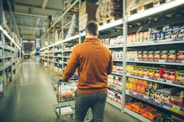 man walk between rows of store.