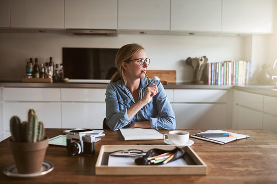 Young female entrepreneur deep in thought while working from hom