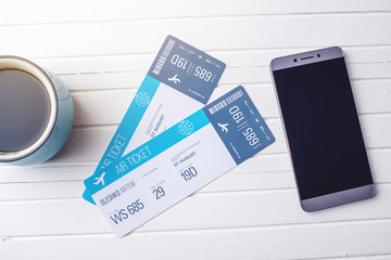 Cup of coffee plane tickets, phone and laptop on white wooden background. Concept of buying the online ticket booking