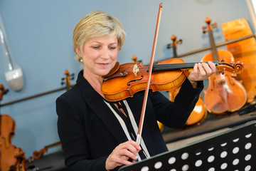 Mature lady practicing violin