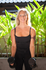 Woman doing an exercise for hands at the tropical gym. beautiful blonde girl with muscles.gym training