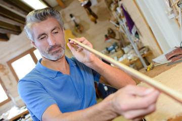 Man making bow for string instrument