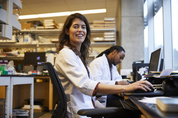 Portrait of confident female researcher smiling while sitting by colleague in laboratory