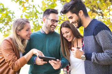 Image of four happy smiling young friends walking outdoors in the park holding digital tablet