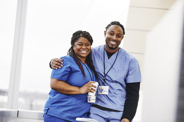 Portrait of confident male nurse standing with arm around female colleague in hospital
