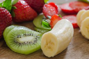 peeled bananas, sliced kiwi and sliced strawberries on a wooden floor