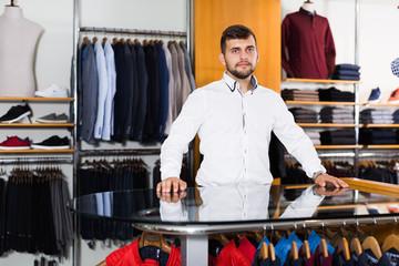 Portrait of positive seller  in men's boutique