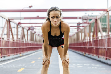 Sporty young woman taking breath after exercise on bridge