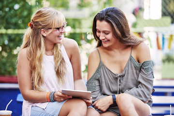 Smiling young women using digital tablet at sidewalk cafe
