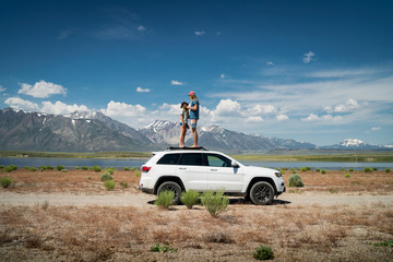 Couple standing on car against mountains, Mammoth Lakes, California, USA