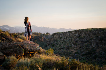 Woman Wrapped In Blanket Standing On Cliff Against Sky