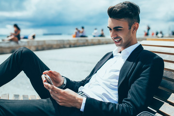 Positive relaxed businessman surfing net outdoors