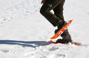 man walks with orange snowshoes on white snow