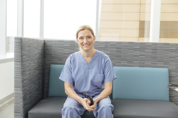 Portrait of smiling mature female nurse sitting on sofa in hospital