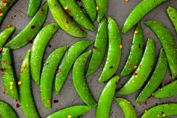 Roasted spicy snap peas. Close up, above view on a baking sheet background.