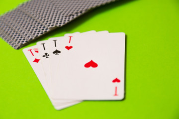 Playing cards over green felt casino background. Four aces.