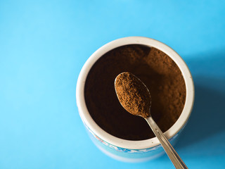 Grinded coffee powder on a spoon over ceramic coffee container