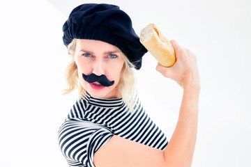 woman dressed as french man with mustache and beret holding  baguette