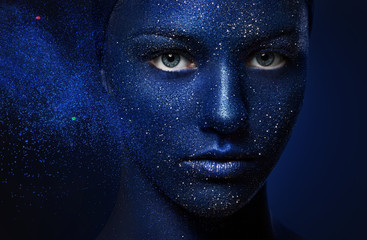 portrait of young beautiful girl. face painted with blue paint and glitter.