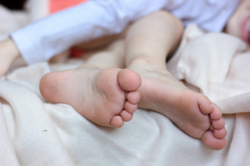 Kid laying in the bed and foot with toes and heels on white blanket.