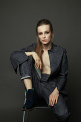 artistic portrait of a woman in a denim suit on a gray background