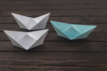 uniqueness concept, paper boat outstanding from the others. Set of origami boats on wooden table