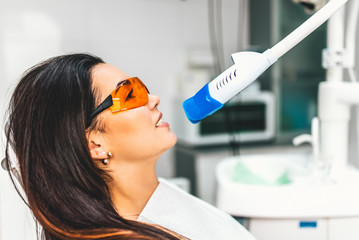 Teeth whitening in dental clinic for pretty female patient