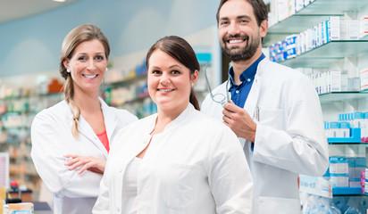 Team von Apothekern in Apotheke steht vor Regalen mit Medikamenten