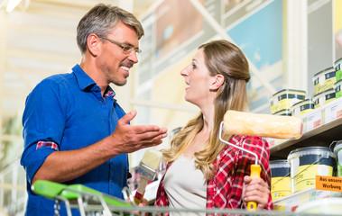 Heimwerker-Paar, Mann und Frau, kauft Farben und Malerwerkzeug für Do-it-yourself-Projekt im Baumarkt