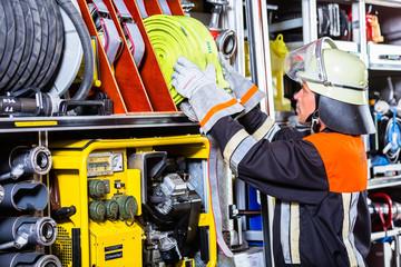 Feuerwehrleute verladen Schläuche in das Einsatzfahrzeug