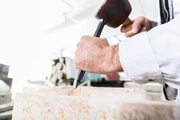 Bildhauer mit Hammer und Meißel beim bearbeiten einer Säule aus Marmor