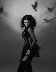 An alien girl in a black, transparent, vintage dress posing against the backdrop of a gloomy forest, which is created by the projector. Artistic black and white photography, play of shadows and light