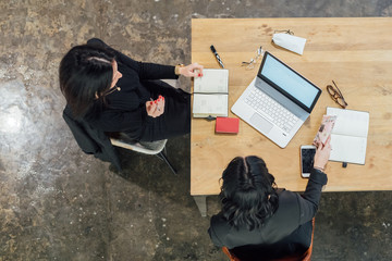 overhead view two young women indoor sitting working desk - business, professional, technology concept