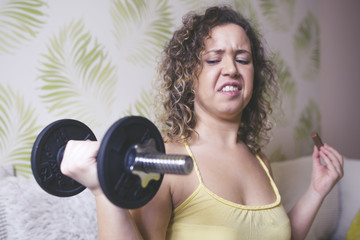 Young woman holding a dumbbell and grimace to it. Give up exercise / training concept